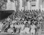 Large group, probably students, sitting on steps, location unknown, n.d.