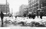 People shoveling snow in Pioneer Square near the pergola and totem pole, Seattle, ca. 1900