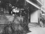 Esther Clein (center, leaning forward) and unidentified friends standing on porch of Clein family...