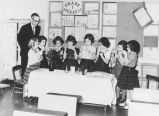 Seattle Talmud Torah 1st grade girls saying prayers at the Sabbath table observed by principal...
