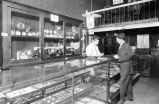 Seattle Luggage Co. interior with Abe Kotkins (left) working at jewelry counter with unidentified...