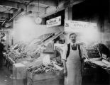 Louis Kaminoff at a produce stand, possibly at the Pike Place Public Market, Seattle, ca. 1920s