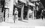 Woman walking past storefront of the Pants Store Co., Seattle, n.d.
