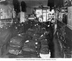 Interior of Boston Clothing Store showing stacks of clothing on table, Ogdensburg, New York, 1899