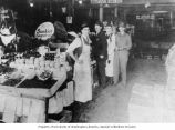 Abe Poll (2nd from right) and unidentified men at produce stand, Westlake Market, Seattle...