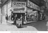 Seamen's Outfitting Store exterior with unidentified man and owner Harold Rogers (right), 1601...