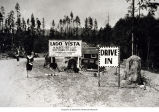 Photo of a sign advertising lots for sale, Lago Vista sales office and ushers, 1928