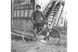 Clyde Dickinson with his bicycle in front of the Nichols and Grothers General Contractors office...