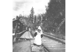 Miriam Kiehl walking along railroad tracks above Snoqualmie Falls, Washington, May 6, 1898