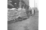 Dog sled team and miners supplies stacked on street in front of J. F. Adams, Alaska Outfitters...