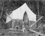 Unidentified man, woman and child including their dog in front of the cooks tent, Alaska, 1909