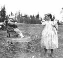 "Laura Kiehl pulling Miriam Kiehl in an ""Iron Clad"" wagon, Magnolia Bluff, Seattle, May..."