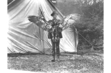 H. Ambrose Kiehl in front of a tent holding dead eagle up by its wings near Fort Seward, Alaska,...