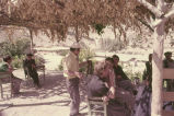 Man talking to men in a cayhani about a woven strap