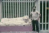 Guard standing by stone sculpture of lion