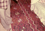 Long kilim with lengthwise zigzags and earring motifs between the zigzags, on the floor by a bed