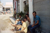 Men sitting on a sidewalk by a florist shop