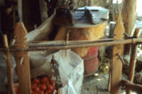 Uprights of a treadle loom and a box of tomatoes