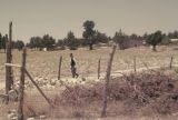 Man walking near barbed wire fence