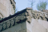 Frieze below the gutter with a lion and faces