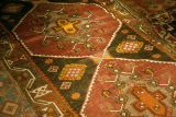 Worn pile weave rug with a cross and floral designs within hexagons