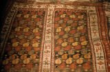 Pile weave rug with two rectangular areas filled with botehs and borders ornamented with s-motifs...