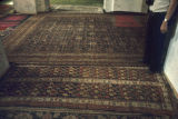 Pile weave rugs on floor of mosque, including one with two rectangular areas filled with botehs...