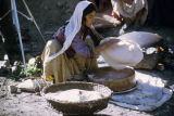 Woman stretching flat bread on the bottom of a cauldron