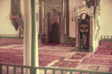 Interior of mosque with mihrab, minbar and rugs