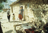 Family and a ground loom in front of a stone house