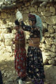 Two Kurdish women spinning with drop spindles