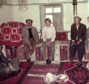 John Landreau and other men in a room with weft float brocade and pile weave rugs