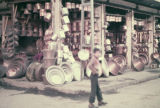 Boy in front of a shop selling copper vessels