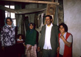 Family in front of a vertical frame loom