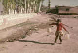Girl carrying water with a yoke