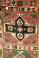 Close up of a pile weave rug with medallions, crosses and stars