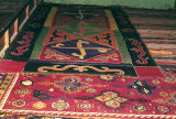 A pile weave rug with quatrefoils and wolf's mouth motifs and an applique rug with swastikas