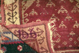 Corner of pile weave rug with earring and tree of life motifs