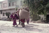 Four women carrying bags of firewood
