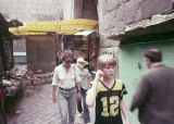 Anita Jester, Christopher and Geoffrey Landreau in the alleys between shops