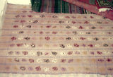 Checked weft float brocade rug with floral patterns in the checks