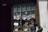 Boy in front of a shop selling copper dishes