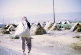 Woman carrying a full bag towards tents filled with chick-pea stalks