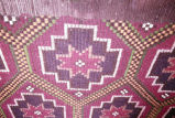 Detail of rug with allover pattern of stars in lozenges on the loom