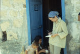Woman researcher talking to a village woman feeding her two children