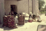 Courtyard with four full bags sitting upright, a millstone and a woman and girl sorting grain in...