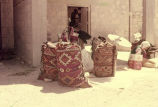 Courtyard with four full bags sitting upright, a millstone and a woman sorting grain in a sieve