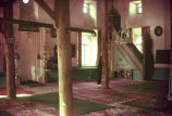 Interior of small mosque with carpeted floor and minbar