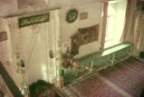 Interior of mosque with mihrab and rugs on the floor