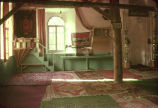 Interior of mosque with minbar, mihrab and rugs